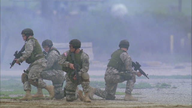 MS, SHAKY, Soldiers holding rifles kneeling back to back on dirt , USA