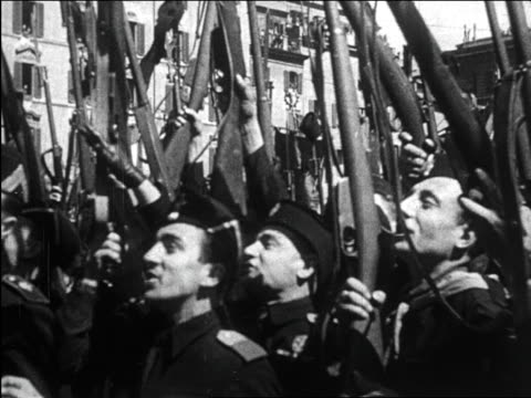 stockvideo's en b-roll-footage met soldiers holding up guns + cheering for mussolini / italy / newsreel - 1930