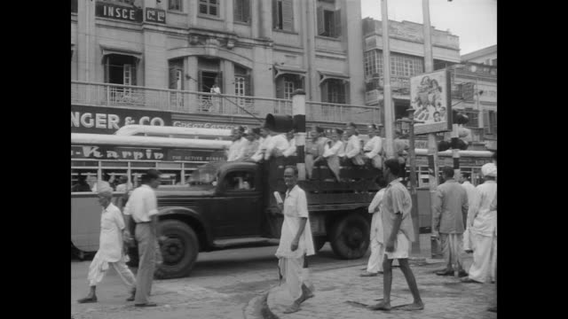 Soldiers in a jeep drive past the Statesman House and the Grand Hotel
