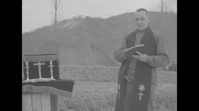 soldiers in a snowy field stand in a semicircle around a chaplain and makeshift altar and they hold open hymnals and sing / the chaplain wearing a... - 礼拝点の映像素材/bロール