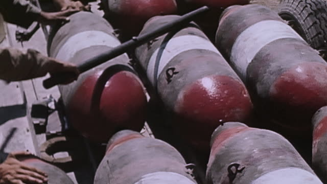soldiers in a vast field rolling bombs along the ground hoisting and loading them onto the back of a flatbed truck / - hoisting stock videos & royalty-free footage