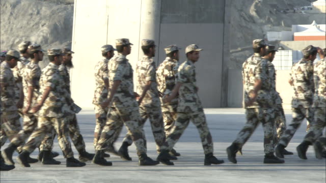 Soldiers in camouflage march through a military base.