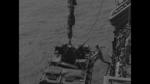 us soldiers in craft on water with cargo net at right / vs troop transport ship with long nets hanging over starboard men climbing down into a... - pacific war stock videos and b-roll footage