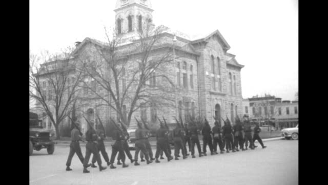 soldiers in distinctive helmets arrive in lampasas, get into formation, and march to courthouse / soldiers enter open door flanked by armed sentries... - cowboy hat stock videos & royalty-free footage