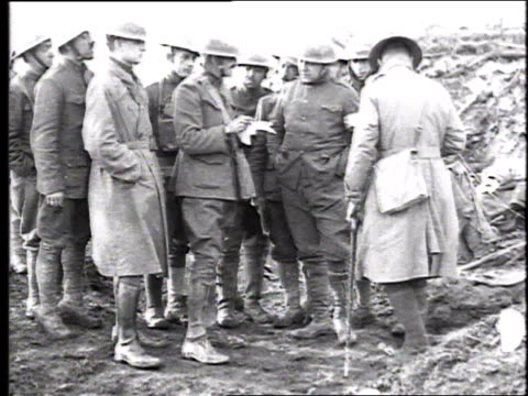 vidéos et rushes de soldiers in field gathering around and listening to soldier reading message then raising fists in air and cheering three times / france - 1918