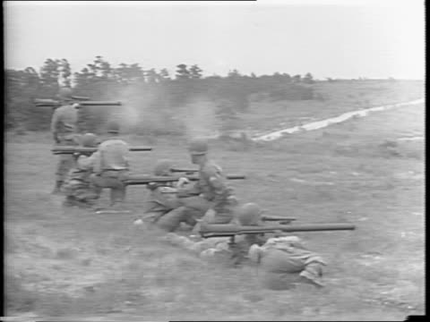 soldiers in field load artillery rounds into bazookas and 57mm rifle / shoulder-held gun is fired next to artillery gun / soldier reloads while he... - rifle stock videos & royalty-free footage