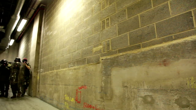 vídeos y material grabado en eventos de stock de soldiers in full uniform and formation move down narrow industrial corridor with weapons raised no - noreste de inglaterra