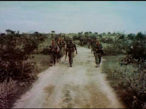 / soldiers in full uniform with guns march along dirt gravel road; two lead larger group, one walks with german shepherd on leash on january 01, 1967... - 犬の綱点の映像素材/bロール