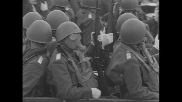 vs soldiers in gas masks are transported by vehicles towing light artillery / vs armored tanks roll in street and pass reviewing stand with king... - ガスマスク点の映像素材/bロール