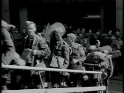 soldiers in gear boarding ship ramp gang plank. soldiers in small 2-man armored vehicle w/ open top passing through town. empty bombers lined up... - 1939 stock-videos und b-roll-filmmaterial