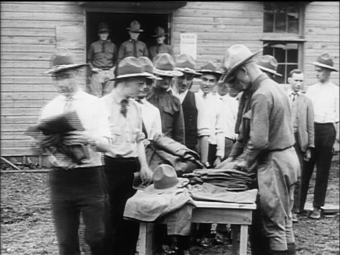 vidéos et rushes de b/w 1917 soldiers in hats being handed uniforms at military training camp / ww i / documentary - uniforme militaire