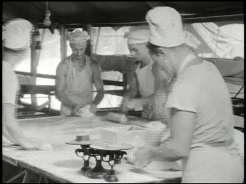 S soldiers in kitchen kneading dough baking bed rolls in large oven VS Hands cutting fruits including tomato amp cantaloupe WWII World War II Pacific...