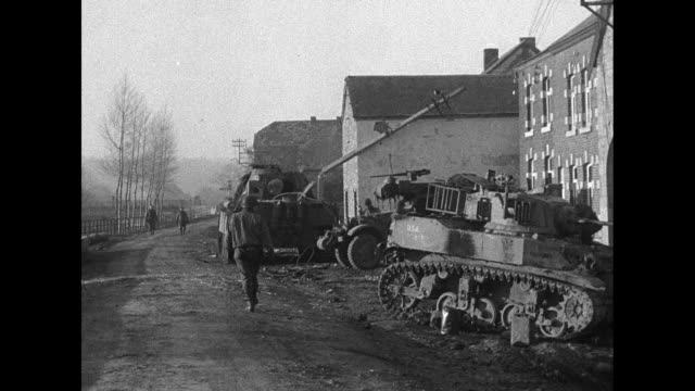 VS US soldiers in position in Belgian village which has been attacked / rear shot soldier walks away on wet road as military vehicles stand by side...
