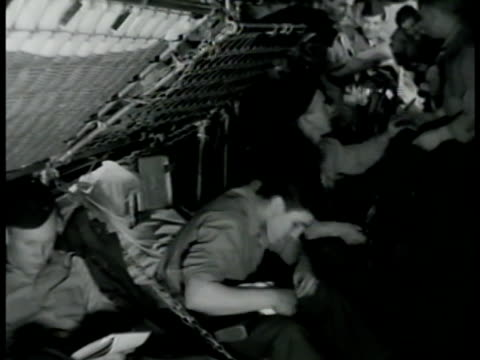 soldiers in tight sleeping quarters cramp cleaning rifles vs men reading talking writing letters playing cards congregating wwii boredom restless usa... - gewehr stock-videos und b-roll-filmmaterial