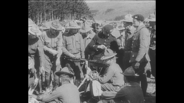 US soldiers in training exercise on hillside in France during World War I / soldiers shown how to assemble stationary machine gun / soldiers load and...