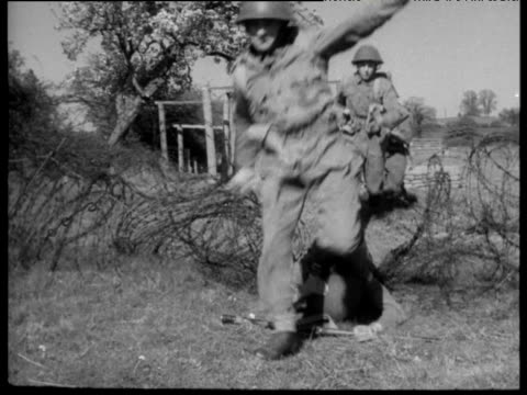 soldiers in uniform wearing hats and carrying guns run towards camera over soldier lying on barbed wire as part of national service training 1956 - run over stock videos & royalty-free footage