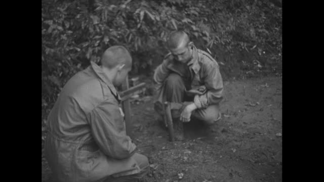 fs soldiers kneel by wooden cross / cu soldier kneels by cross with japanese characters on it / note exact day not known - prisoner of war stock videos & royalty-free footage