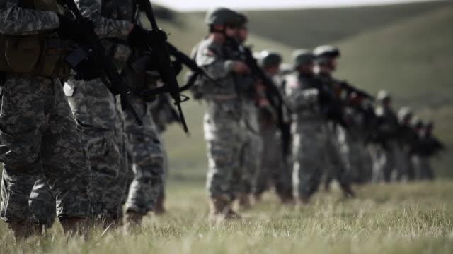 soldiers kneel to fire rifles - us militär stock-videos und b-roll-filmmaterial