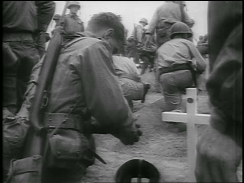 soldiers kneeling by soldiers' graves with crosses / korean war / newsreel - credente video stock e b–roll