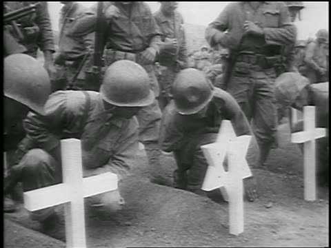 stockvideo's en b-roll-footage met b/w 1950 soldiers kneeling by soldiers' graves with crosses star of david / korean war / newsreel - koreaanse oorlog