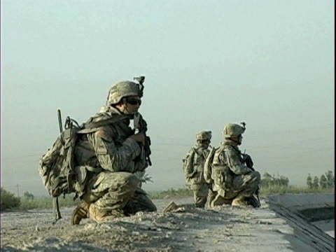 US soldiers kneeling near canal in rural area / Arab Jabour Iraq / AUDIO