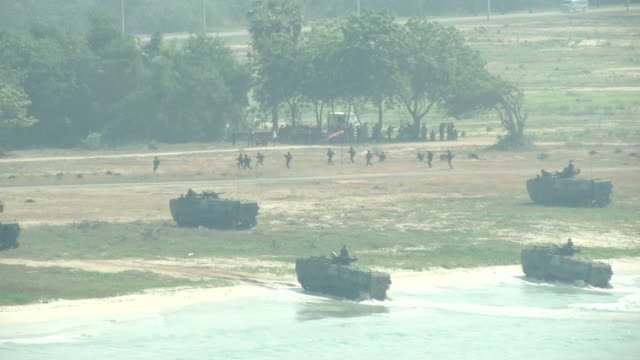 soldiers land with an amphibious assault vehicles and secure the beachhead during the ongoing usthai joint military exercise titled cobra gold on hat... - amphibienfahrzeug stock-videos und b-roll-filmmaterial