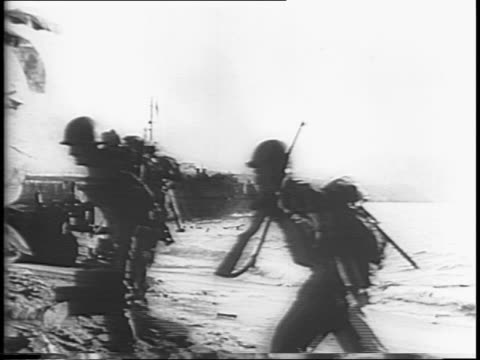 Soldiers landing on the beaches of New Guinea / some soldiers slip and fall exiting landing barges / soldiers run along beach and move through...