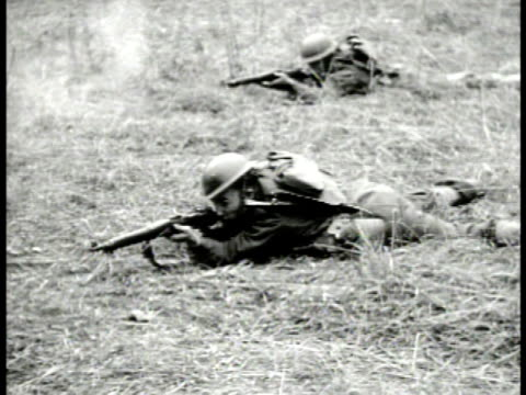 soldiers laying on grass field firing rifle. infantry running across grassy field tree fg. wwii - allied forces stock videos & royalty-free footage