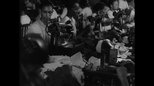 soldiers leading mules through streets. workers making shoes: sewing leather stitching heel on machine. workers at row of desks w/ papers. burlap... - 荒い麻布点の映像素材/bロール