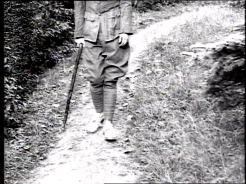 CU soldier's legs limping with a cane along a path / France