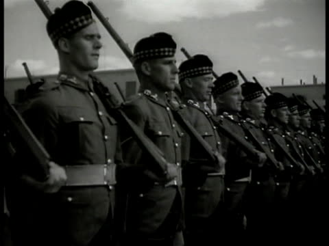 soldiers lined up doing regiment drill. soldiers in warm-weather uniform marching down hill buildings bg. armed soldiers marching on beach . british... - 連隊点の映像素材/bロール