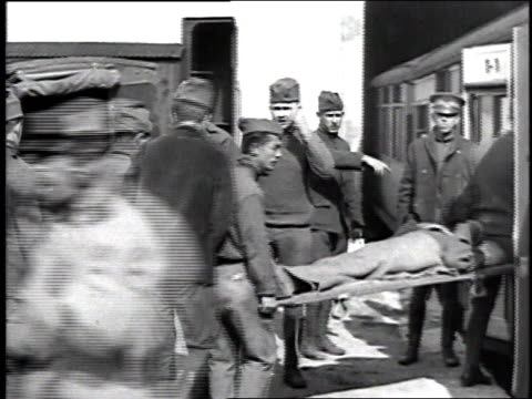 soldiers loading a wounded soldiers on a stretcher from an ambulance onto a train for evacuation from the front region / france - 1918 stock videos & royalty-free footage