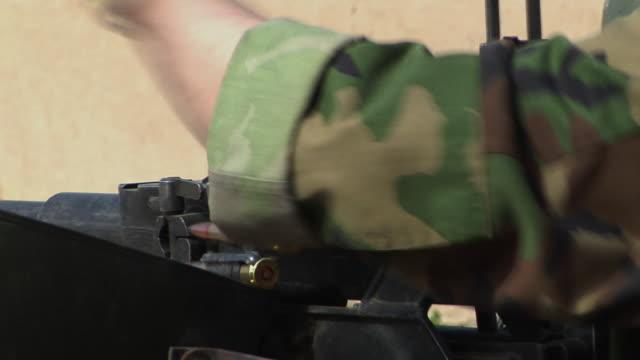 cu soldiers loading bullets in gun / afghanistan - 2001年~ アフガニスタン紛争点の映像素材/bロール