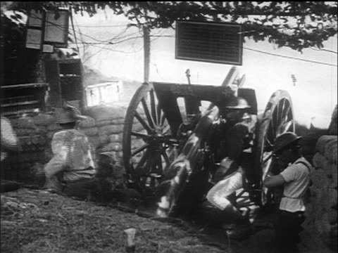 b/w 1917/18 soldiers loading cannon shooting it during world war i / newsreel - artiglieria video stock e b–roll