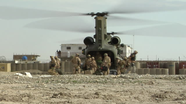 soldiers loading luggage in military helicopter / musa qala, helmand province, afghanistan. - british military stock videos & royalty-free footage