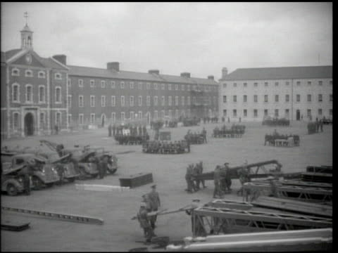 soldiers loading steel beams in yard lined w/ buildings others working on trucks more standing in groups bg ws tanks traveling edge of forest road... - pontoon bridge stock videos and b-roll footage