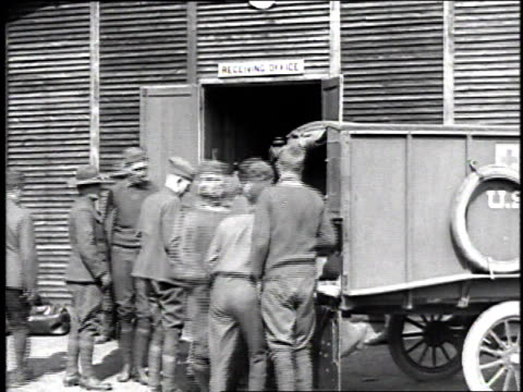 soldiers loading wounded soldiers on stretchers into an ambulance / france - 1918 stock videos & royalty-free footage