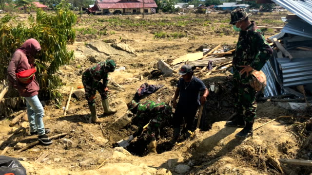 Soldiers look on as a man digs for the body of a woman buried beneath mud following an earthquake and tsunami on October 04 2018 in Palu Indonesia...