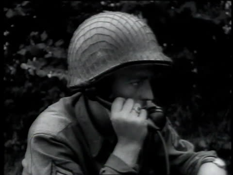 Soldiers look through binoculars as one talks on the telephone Large bulldozer tanks with chains hanging off front drive down the road / Normandy...