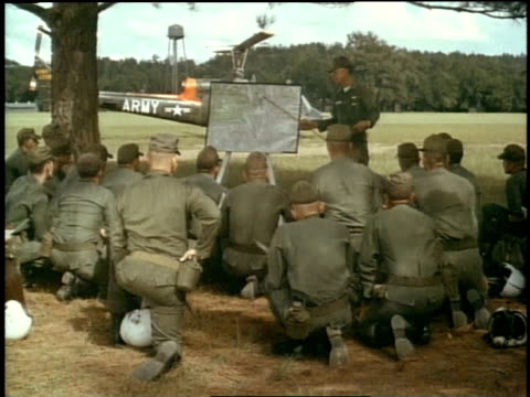1967 MONTAGE soldiers looking at a notepad as one points at it, many helicopters flying close together and low to the ground / Fort Campbell, Kentucky, United States