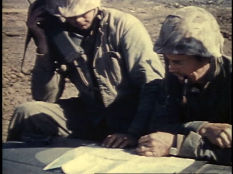 Soldiers looking at map talking on phone and driving tanks / Iwo Jima Japan