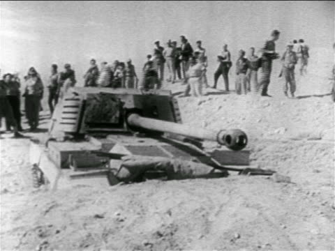vídeos de stock e filmes b-roll de soldiers looking at tank half buried in sand in desert / suez crisis / middle east - 1956
