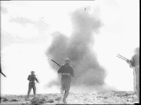 Soldiers lying on ground explosions in the distance / closeup on soldier with binoculars / soldiers running towards billowing smoke cloud