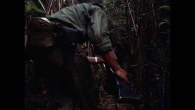 soldiers making their way through the jungle during the vietnam war war as wounded troops are evacuated from combat zone near the 17th parallel.... - vietnam war stock videos & royalty-free footage