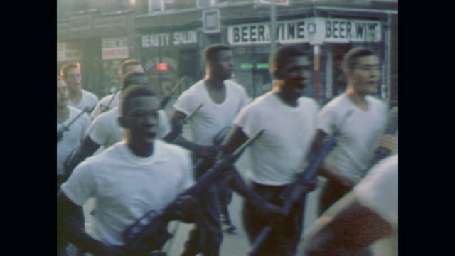 soldiers march double time down city street carrying rifles during drill exercises - 1967 bildbanksvideor och videomaterial från bakom kulisserna