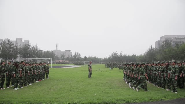 Soldiers march in a grassy field during military training.