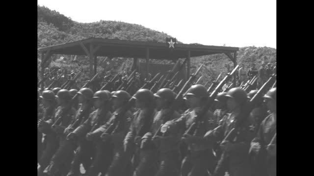 Soldiers march past camera in formation prior to departure from Korea at the end of the Korean War / soldiers march past reviewing stand / view from...