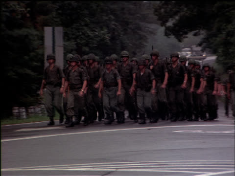 Soldiers march past the entrance for West Point.