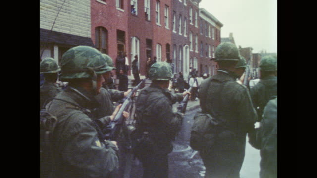 Soldiers march with rifles out down Baltimore city street / Black residents watch from the sidewalk