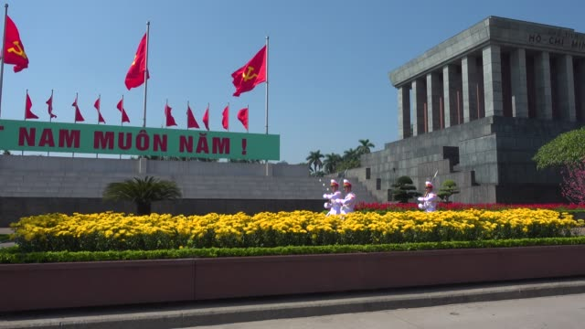soldiers marching at ho chi minh mausoleum. hanoi, vietnam. tourist walking along the big square. red communist and vietnamese flags waving - waving icon stock videos & royalty-free footage